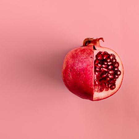 Frutta rossa di melograno su sfondo rosa pastello. Minimo concetto pianeggiante. Archivio Fotografico
