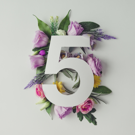 Creative layout with colorful flowers, leaves and number five. Anniversary concept.Flat lay.