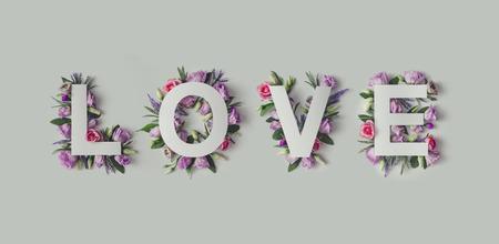 カラフルな花、葉、愛という言葉で創造的なレイアウト。愛の概念。フラットが横たわっていた。