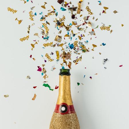明るい背景に紙吹雪と黄金のシャンパン ・ パーティ ボトル。フラットが横たわっていた。コンセプトを祝います。