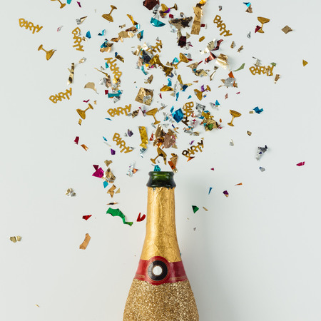 Golden champagne party bottle with confetti on bright background. Flat lay. Celebrate concept.