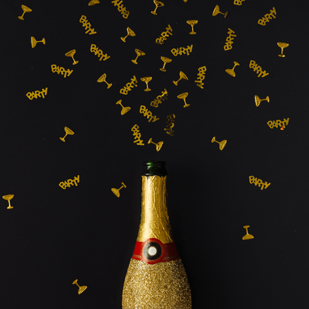alcohol drinks: Golden champagne party bottle with confetti on dark background. Flat lay. Celebrate concept.