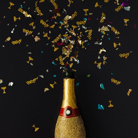 暗い背景に紙吹雪と黄金のシャンパン ・ パーティ ボトル。フラットが横たわっていた。コンセプトを祝います。