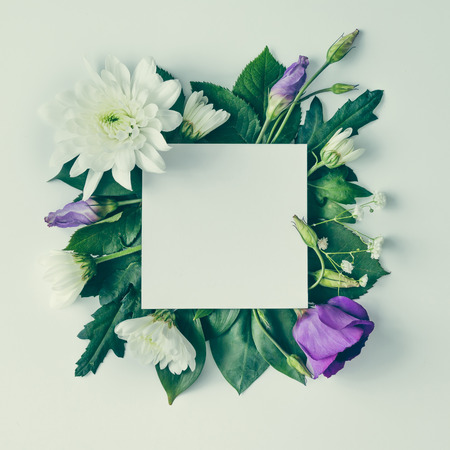 Creative layout made of flowers and leaves with paper card note. Flat lay. Nature concept Stock Photo - 70329936