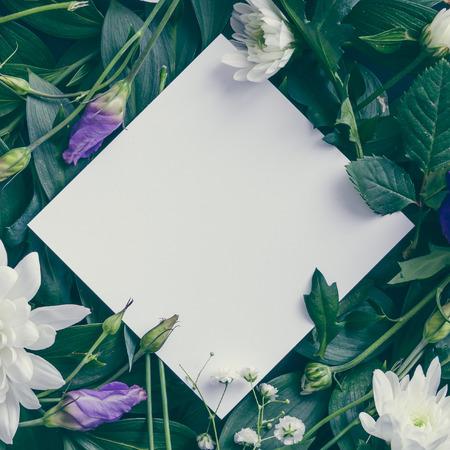 Layout criativo feito de flores e folhas com nota de papel. Leito plano. Conceito de natureza