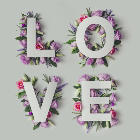 Creative layout with colorful flowers, leaves and Word LOVE. Love concept.Flat lay.
