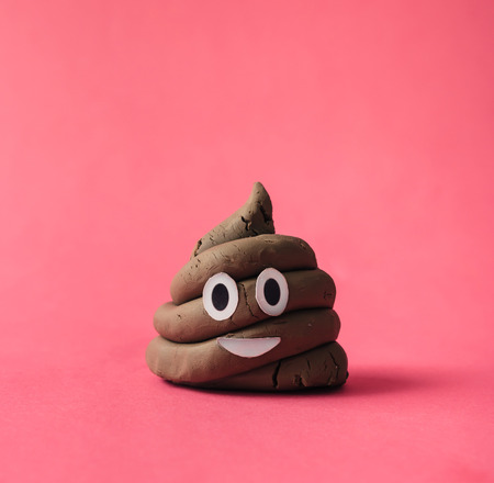 Poop emoticon on pink background.