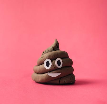 Poop emoticon sobre fondo de color rosa. Foto de archivo