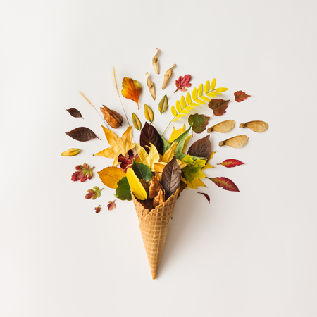 Colorful bright creative layout. Ice cream cone with autumn leaves. Flat lay.