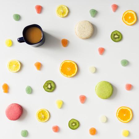Modèle coloré de fruits lumineux avec une tasse de café et des bonbons sur fond blanc. Plat poser. Banque d'images