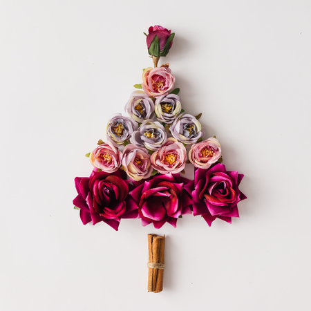 Christmas tree made of flowers and cinnamon sticks. Flat lay. Holiday concept.