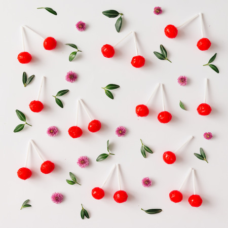 Colorful pattern made of red cherry lollipops, leaves, and flowers. Flat lay. Fruit concept. Zdjęcie Seryjne