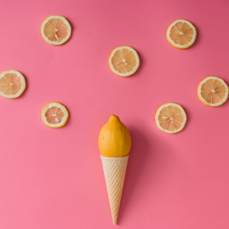 minimal: Lemon fruit in ice cream cone with lemon slices on pink background. Minimal concept. Flat lay.