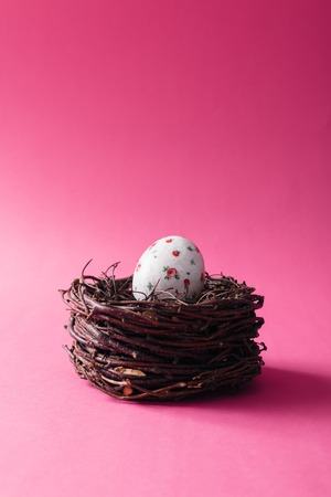 Decorated Easter egg in nest on pink background Stock Photo