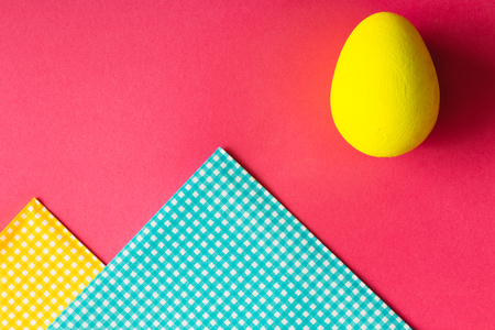 Top view of Easter egg and napkins on pink background