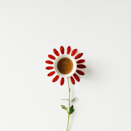 커피 컵과 꽃 꽃잎입니다. 최소한의 개념. 평평한 평신도.
