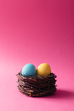 Decorated Easter eggs in nest on pink background