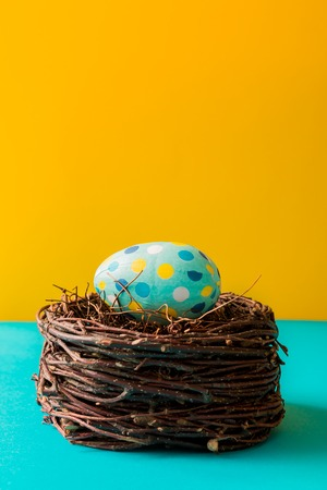 coloridos huevos de Pascua en el nido sobre fondo amarillo y cian Foto de archivo