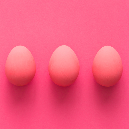 Top view of three pink eggs on pink background Stock Photo