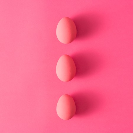 Top view of three pink Easter eggs on pink background Stock Photo