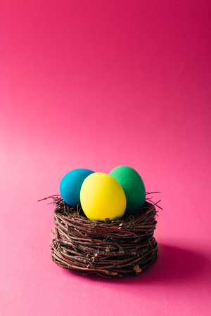 Colorful Easter eggs in bird nest on pink background
