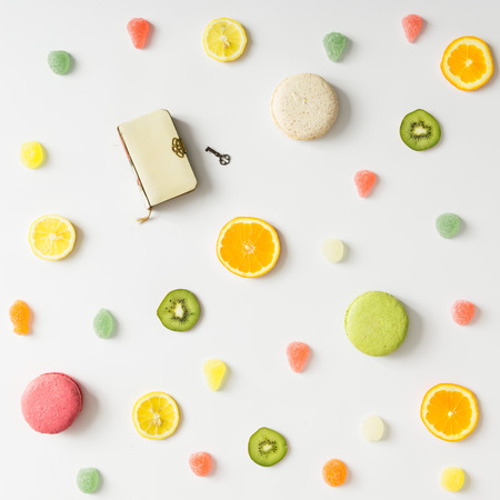 Colorful bright fruit pattern with old book and sweets on white background. Flat lay. Stock Photo