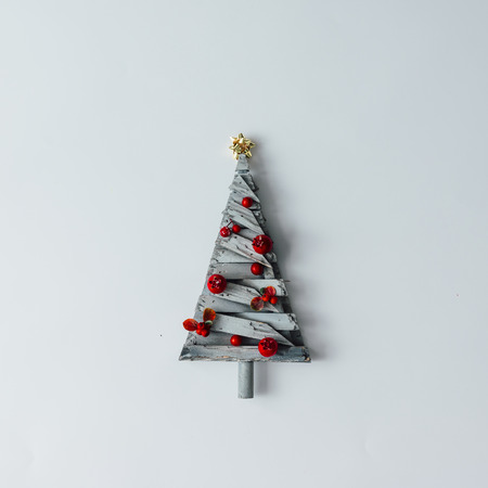 Minimalistic Christmas tree made of wood on white background. New Year concept. Flat lay.