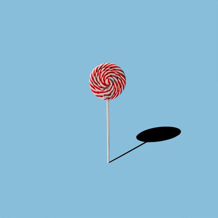 Lollipop on blue background. Minimal concept Imagens
