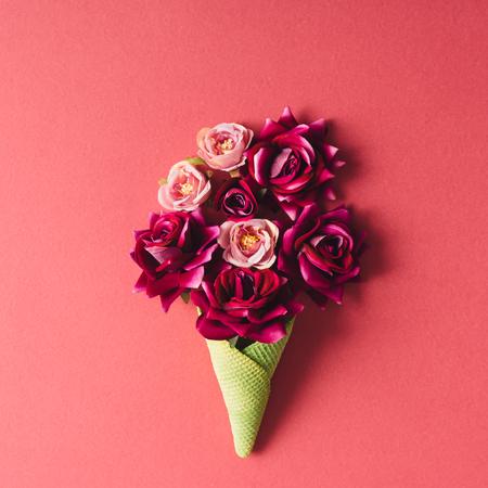 Lila virágok és zöld fagylalt kúp rózsaszín háttér. Lapos feküdt.