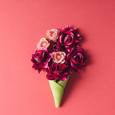 Purple flowers and green icecream cone on pink background. Flat lay. Stock Photo