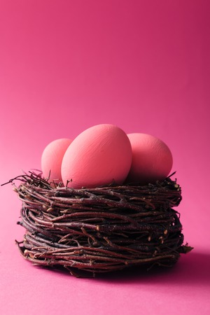 Pink Easter eggs in nest on pink background