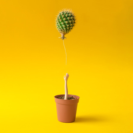 Doll hand reaching for cactus balloon out of flower pot on yellow background. Creative minimal concept. Standard-Bild