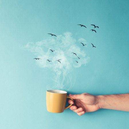 morning breakfast: Coffee cup with steam, clouds and birds. Coffee concept. Flat lay.