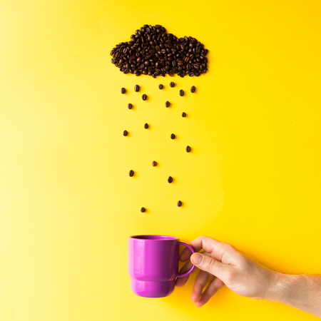 Coffee beans in shape of rainy cloud with purple cup on yellow background. Weather concept.