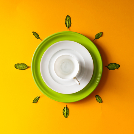 Empty tea cup with green leaves  on orange background. Time concept.