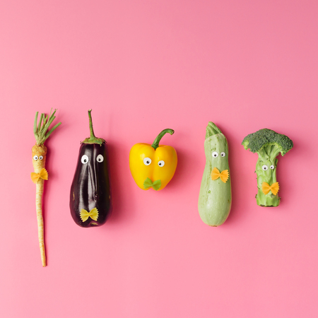 Various vegetable characters on pink background. Minimal concept.
