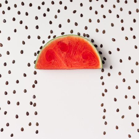Fatia de Watermellon com sementes chovendo. Leito plano. Conceito do tempo.