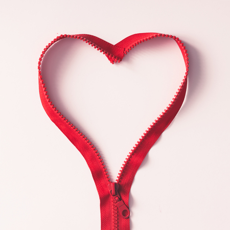 Red zipper in shape of a heart on white background. Flat lay