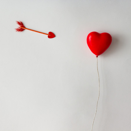 Red heart shaped balloon with cupid arrow on white background. Love concept. Flat lay.