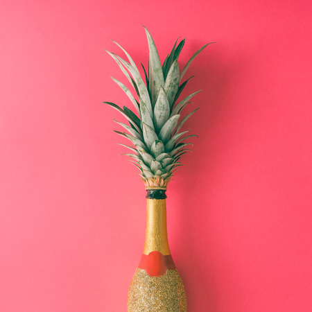 Champagne bottle with pineapple leaves on pink background. Flat lay. Minimal party concept. Stockfoto