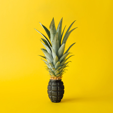 Grenade bomb with pineapple leaves on bright yellow background. Minimal fruit concept. Archivio Fotografico