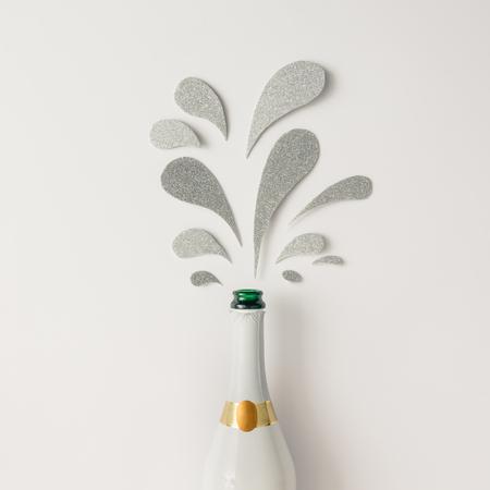 きらびやかなシルバーとシャンパンのボトルは、白い背景の上はね。フラットが横たわっていた。最小限の党概念。