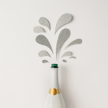 Champagne bottle with silver glittering splashes on white background. Flat lay. Minimal party concept.