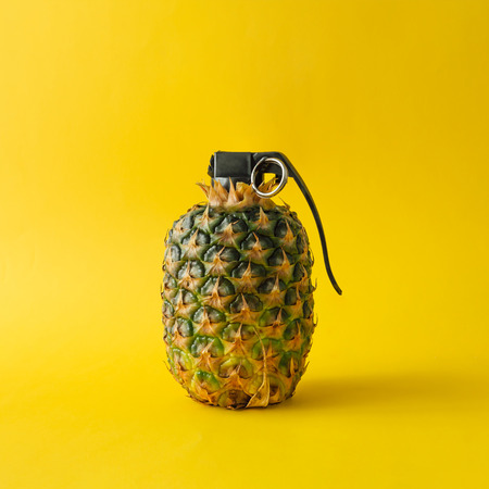 明るい黄色の背景にパイナップル爆弾。最小限の果物概念。