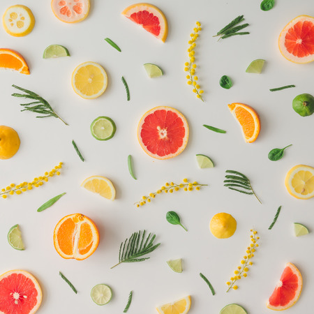 Colorful food pattern made of lemon, orange, grapefruit and flowers. Flat lay. Banco de Imagens