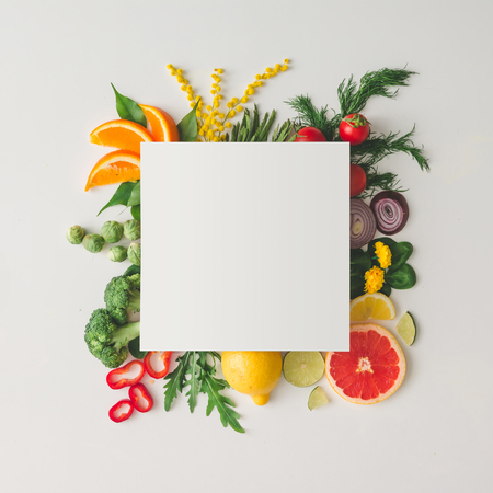 Creative layout made of various fruits and vegetables with white paper card. Flat lay. Food concept. Archivio Fotografico