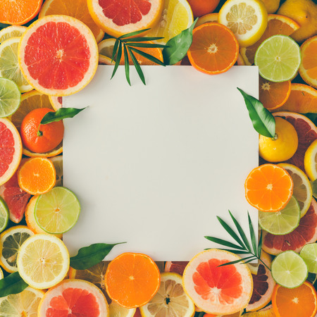 Creative layout made of fruits with white paper card note. Flat lay. Tropical concept. Archivio Fotografico