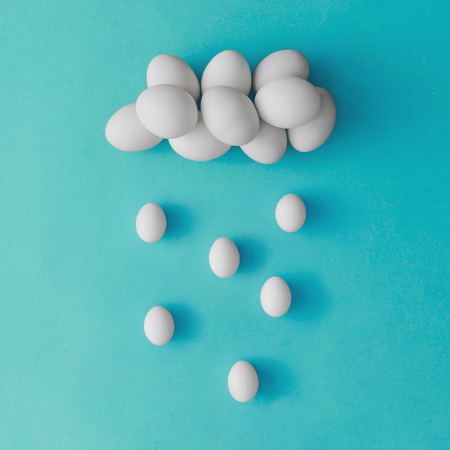 Cloud and rain made of easter eggs on blue background. Flat lay. Minimal concept. Imagens