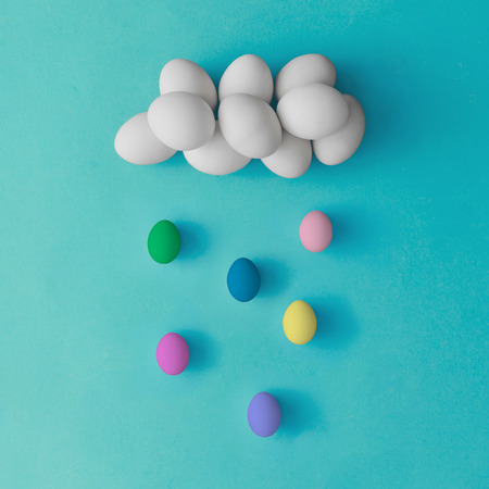 minimal: Cloud and rain made of colorful easter eggs on blue background. Flat lay. Minimal concept.