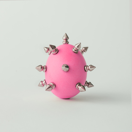 Pink Easter egg with metal thorns. Minimal concept.